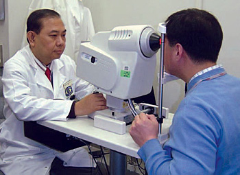 Doctor examining a patients eyes through a machine.