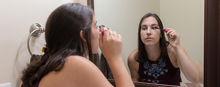 Woman putting on mascara as she looks in the mirror