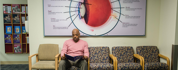 Man sitting and reading a magazine in a clinic waiting room underneath a large diagram of an eye that hangs on the wall