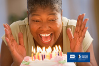 Woman smiling at the cake with burning candles. NIH, National Eye Institute. NEHEP, National Eye Health Education Program.