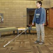The co-robotic cane includes a motorized roller tip that guides the user. The photo shows a man standing in a building lobby with his arm outstreached holding a cane. The can has a white roller ball tip and a box and wires near the handle.