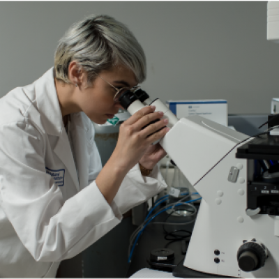 female scientist looking through microscope