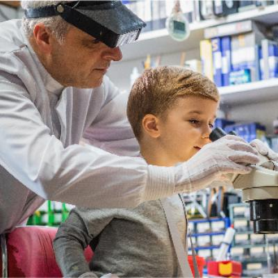 scientist helps boy look through a microscope