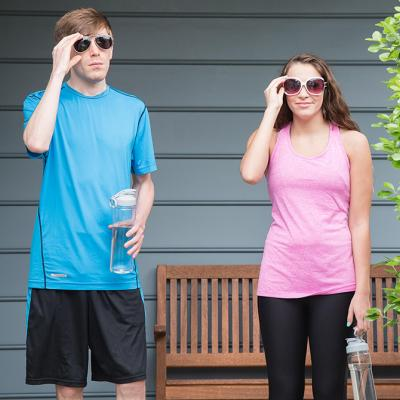 Two people with sunglasses stand in front of bench with work out clothes and water bottles