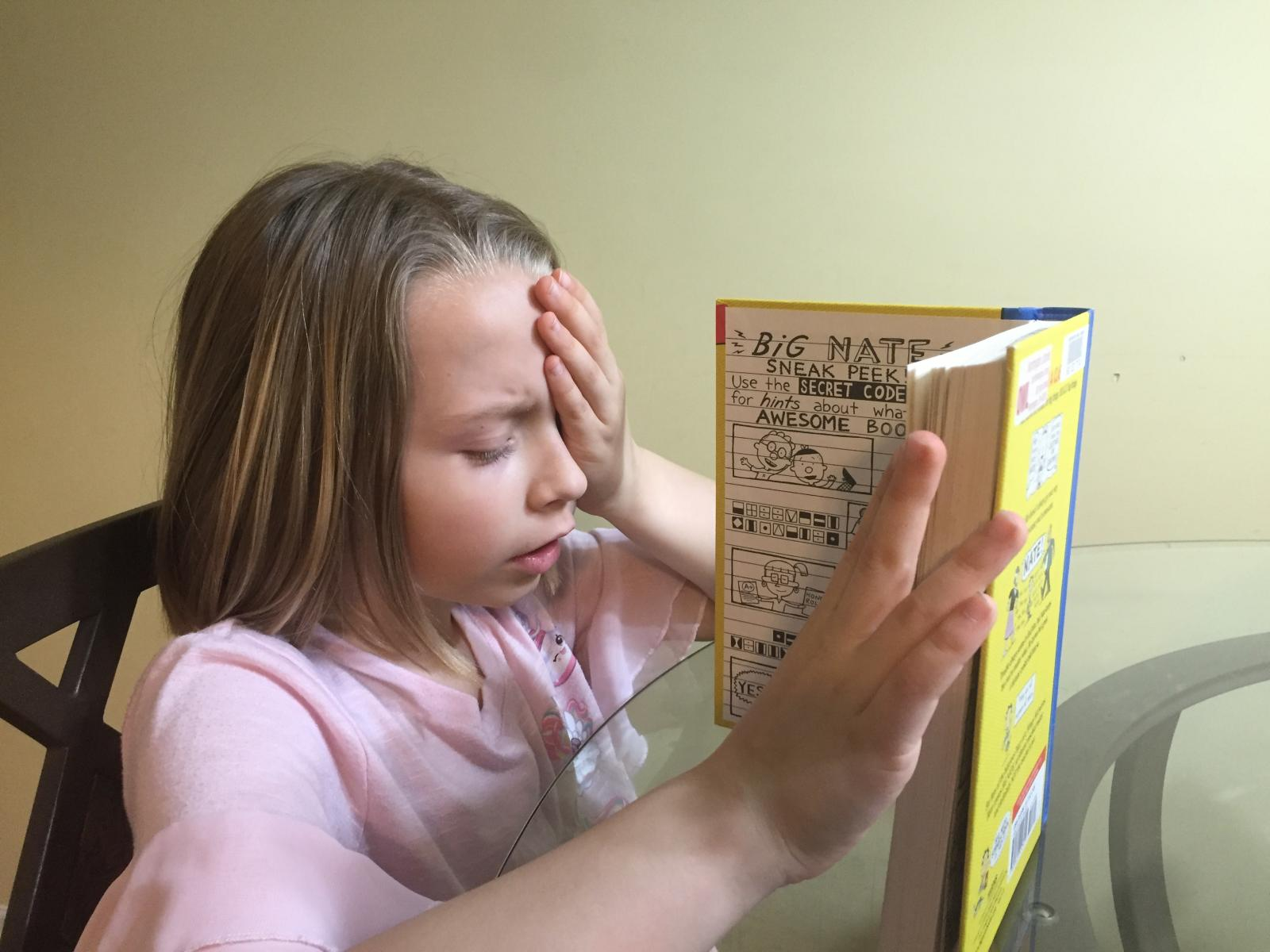 Child reading book with one hand covering an eye
