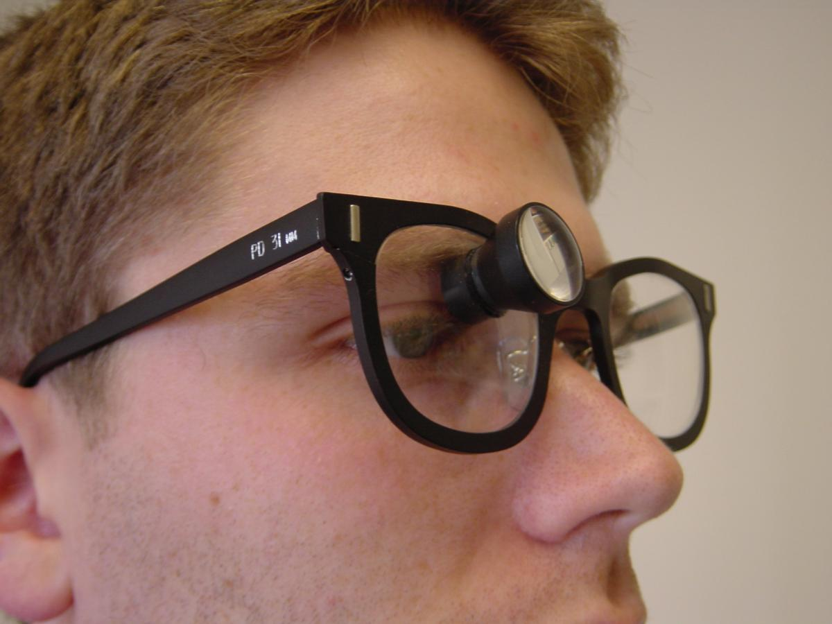 Man wearing glasses with magnifier over one eye