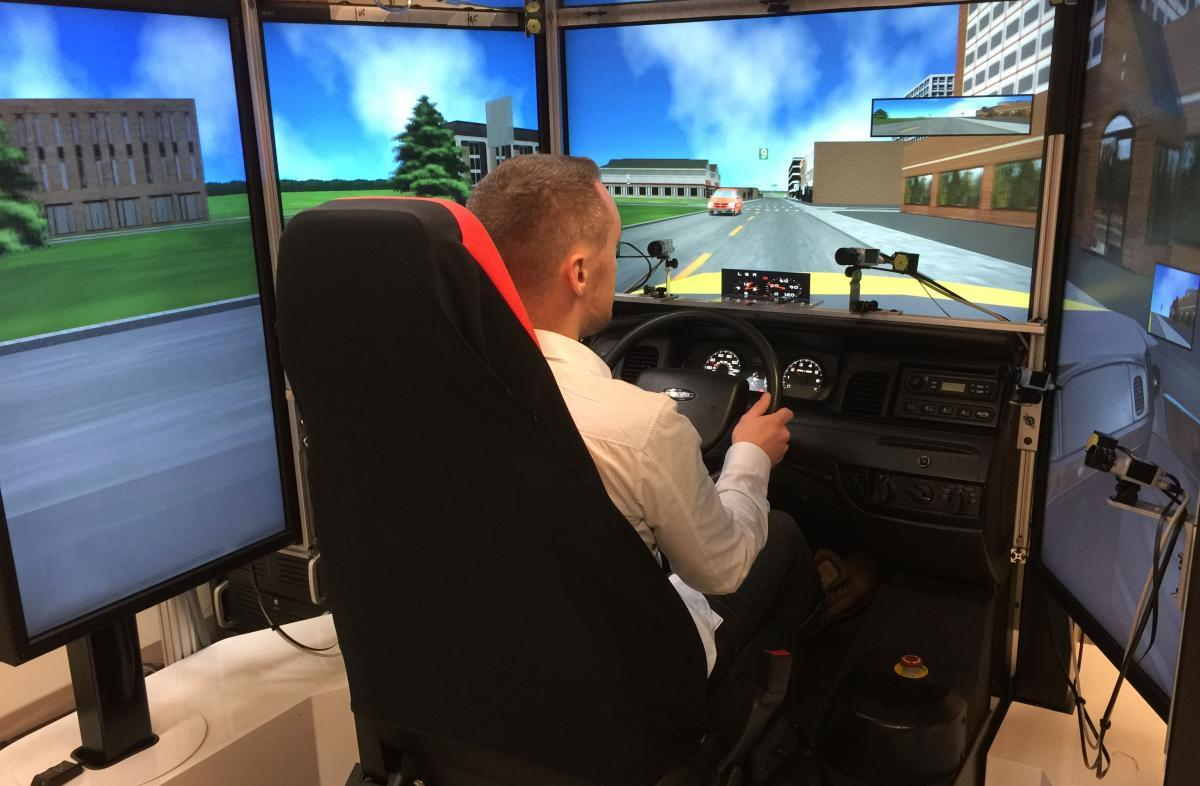 Man at controls with screens surrounding him