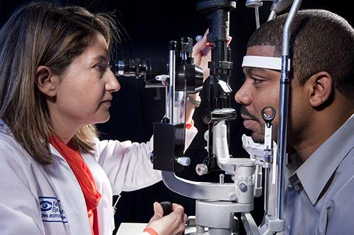 Doctor examines patient's eye using slit lamp