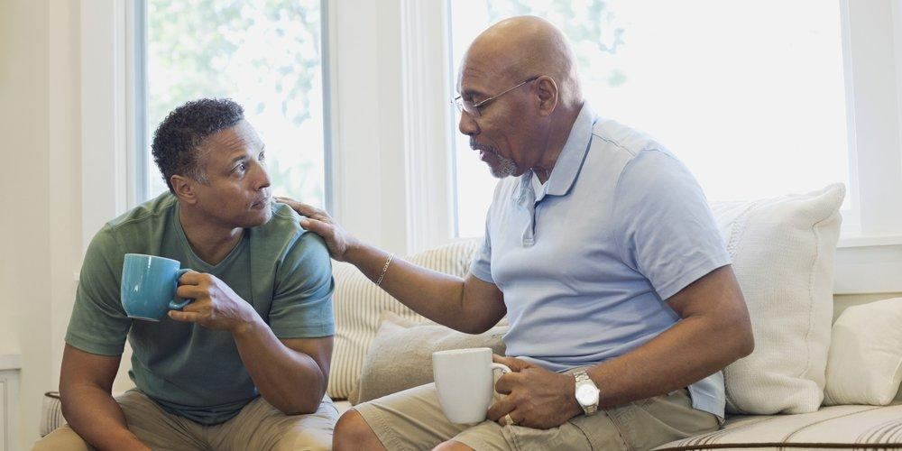 An African American elder father and middle aged son drinking coffee and talking.