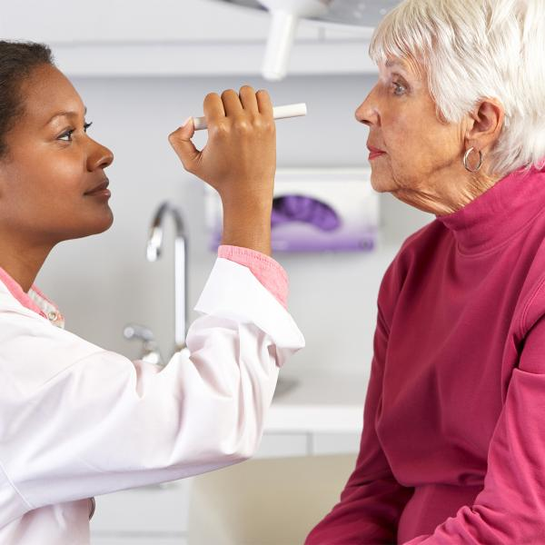 Doctor examining an elderly woman's eyes with a pen light