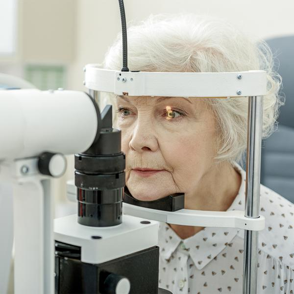 An elderly woman has her eye examined using a slit lamp