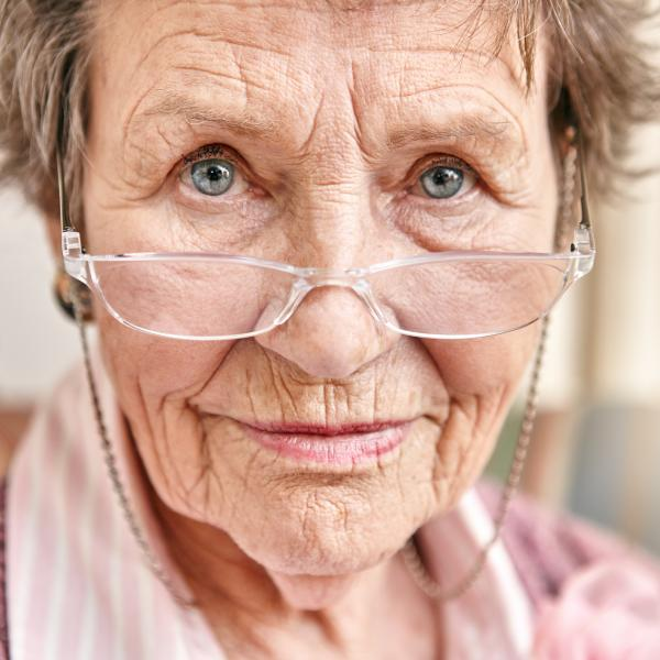 Elderly woman wearing reading glasses looks at the camera