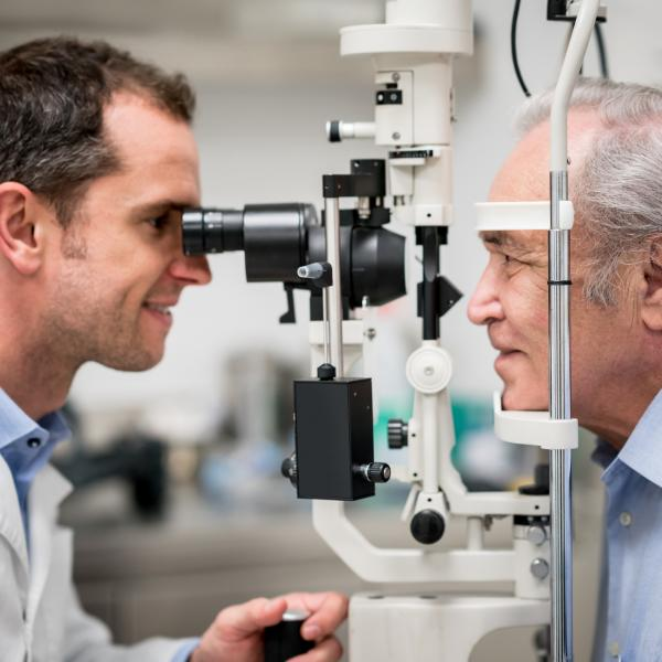 Elderly man has his eyes examined by a doctor