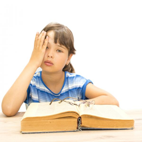 Child covering eye, with glasses lying on top of book