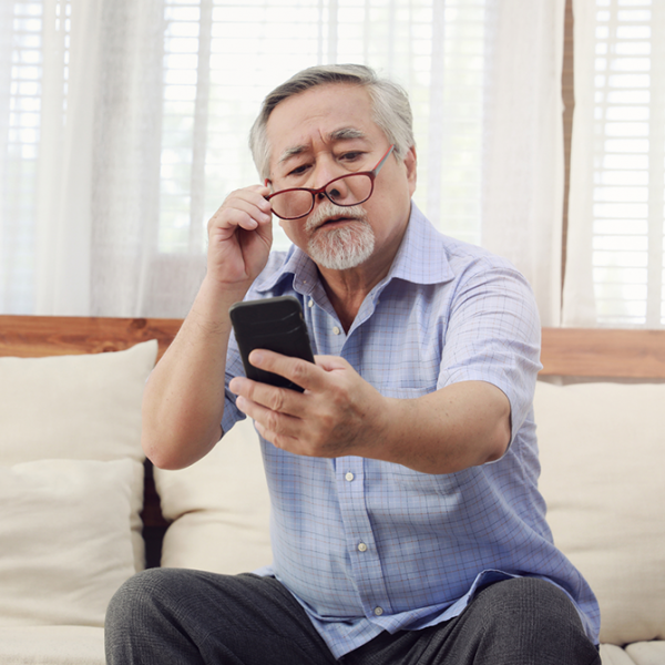 A man with presbyopia holding a phone away from his face so he can see it