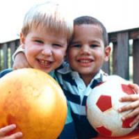 2 young boys hold balls and smile at the camera