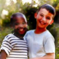 Two boys smile at the camera. Asymmetric dark spots block parts of the image, representing vision loss from diabetic retinopathy.