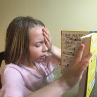 Girl reading book, with hand over one eye