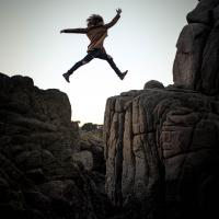 person leaping across rock crevice. Credit: Sammie Vasquez Upsplash