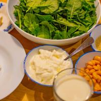 Greens, beans and dairy products arranged on a table